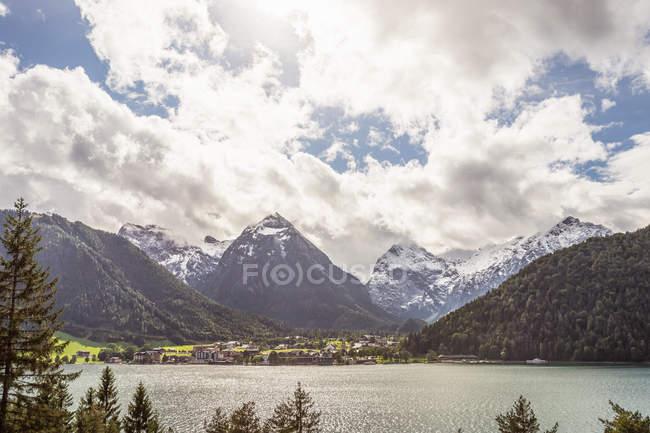 Vista del lago y las montañas bajo el cielo nublado - foto de stock