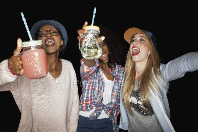 Young women holding mason jars arms raised open mouthed smiling — Stock Photo
