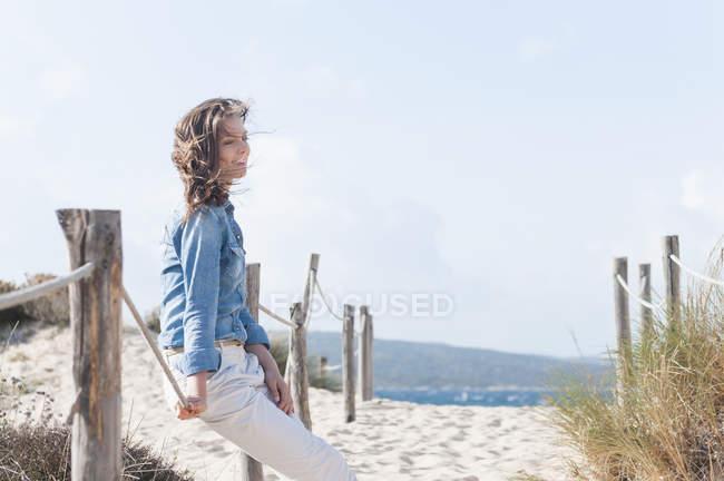 Mitte Erwachsene Frau sitzen auf Seil eingezäunten Weg, Sardinien, Italien — Stockfoto