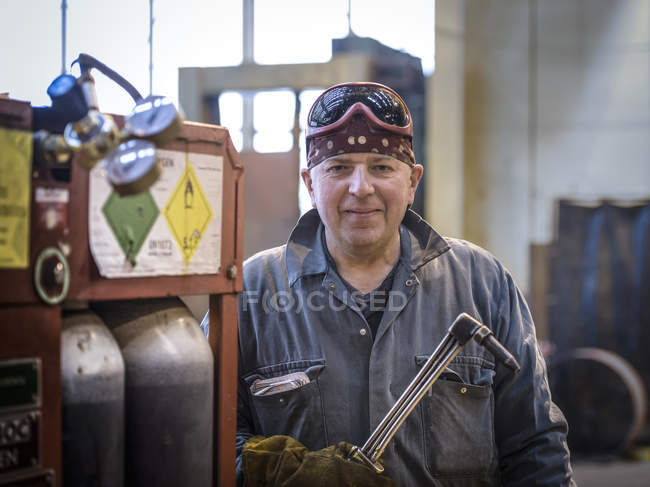Portrait of welder in overalls and safety goggles in factory — Stock Photo
