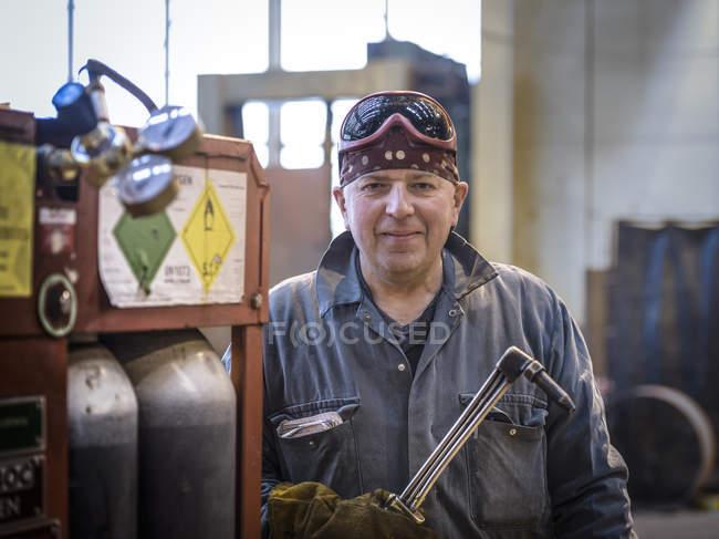 Portrait de soudeur en salopette et lunettes de sécurité en usine — Photo de stock