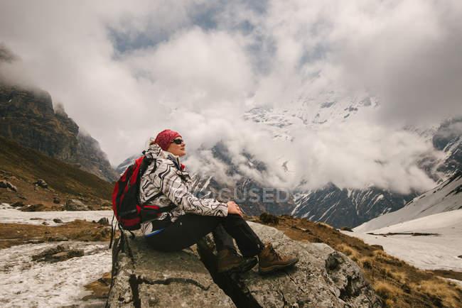 Donna che si siede sulla roccia guardando vista, trek Abc (Annapurna Base Camp trek), Nepal — Foto stock