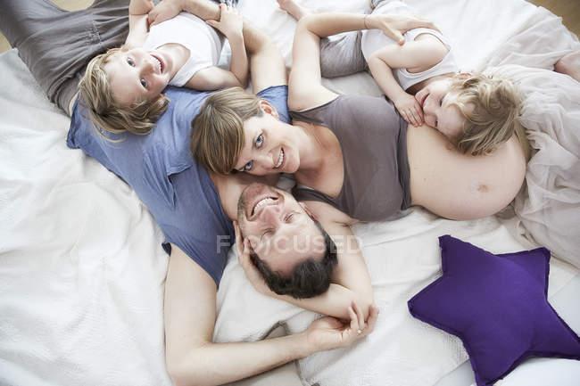 Вагітна мати з сім'єю, лежачи на ліжку — стокове фото