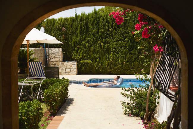 Дівчинка-підліток розслабляючий на надувних свято апартамент поплавати в басейні — стокове фото
