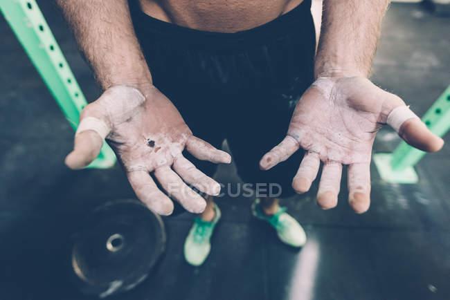 Nahaufnahme von männlichen Crosstrainern mit Kreidehänden im Fitnessstudio — Stockfoto
