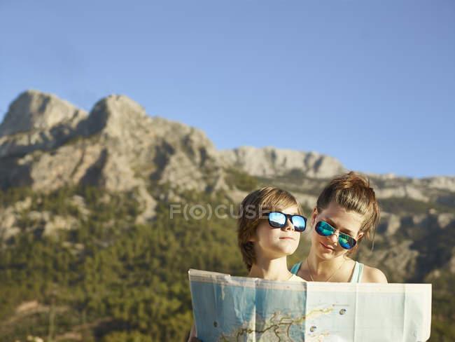 Ragazza e fratello adolescenti guardando la mappa, Maiorca, Spagna — Foto stock