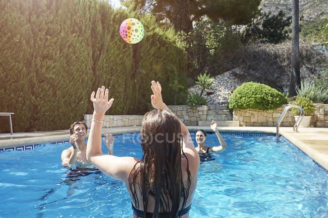 Ragazza adolescente che lancia palla a madre e fratello in piscina — Foto stock