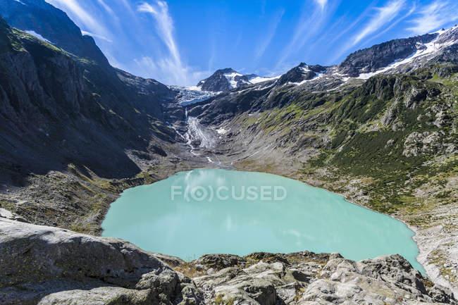 Lago di Trift circondato da montagne sotto cielo blu — Foto stock