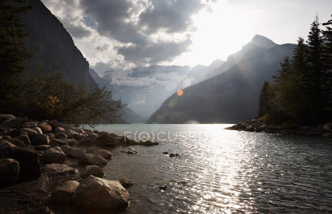 Rocky shore of mountain river with sunlight reflecting in water — Stock Photo