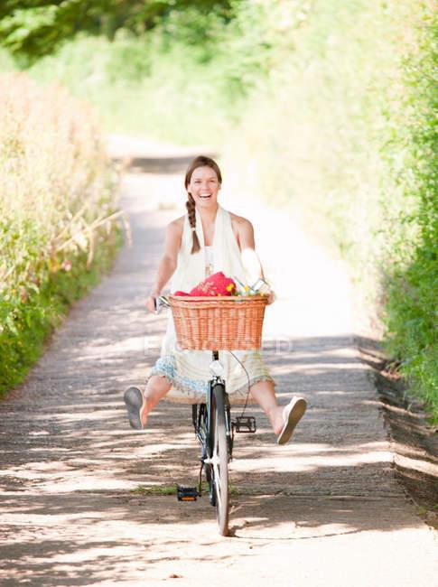 Mulher pedalando na pista de campo — Fotografia de Stock