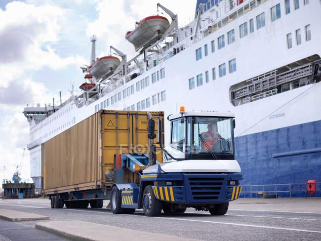 Shipping containers and truck by ship in port — Stock Photo