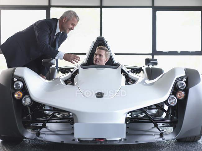 Verkäufer mit Kunden Supersportwagen im Show-room — Stockfoto
