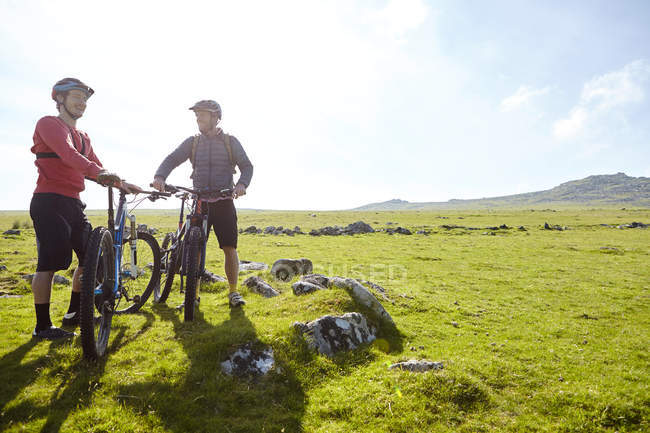 Cyclists on hillside holding bicycles chatting — Stock Photo
