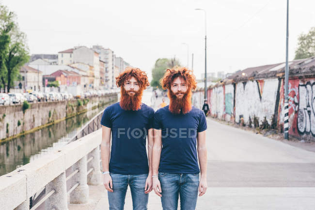 Portrait of young male hipster twins with red hair and beards standing on bridge — Stock Photo