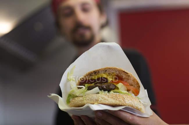 Young man serving hamburger from fast food van — стокове фото