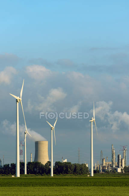 Wind turbines with nuclear smokestack — Stock Photo