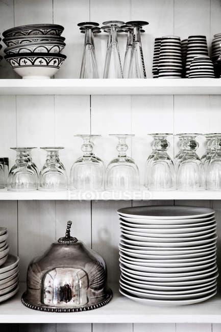 Estantes con vasos, platos y cuencos - foto de stock