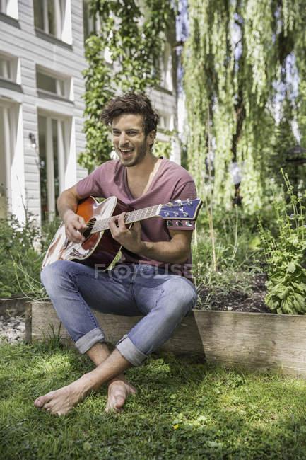 Молодой человек играет на гитаре в саду — стоковое фото