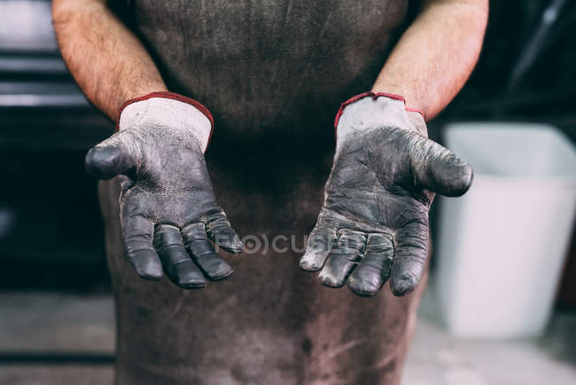 Mid section of metalworker protective gloves in forge workshop — Stock Photo