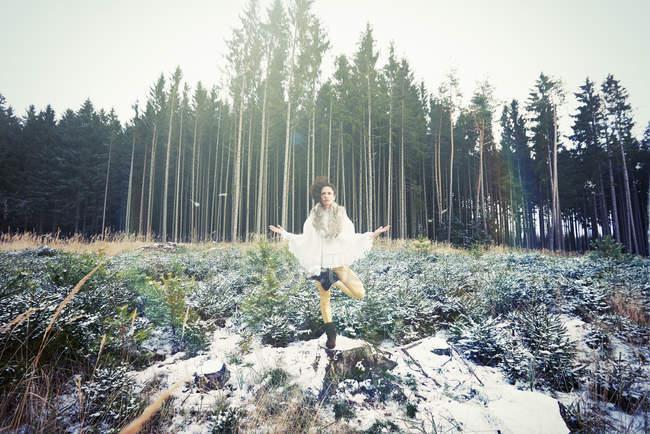 Середині дорослої жінки, які практикують йогу стоячи дерево створюють у лісі — стокове фото