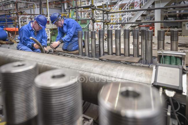 Инженеры, работающие над ремонтом корпуса турбины во время отключения электростанции — стоковое фото