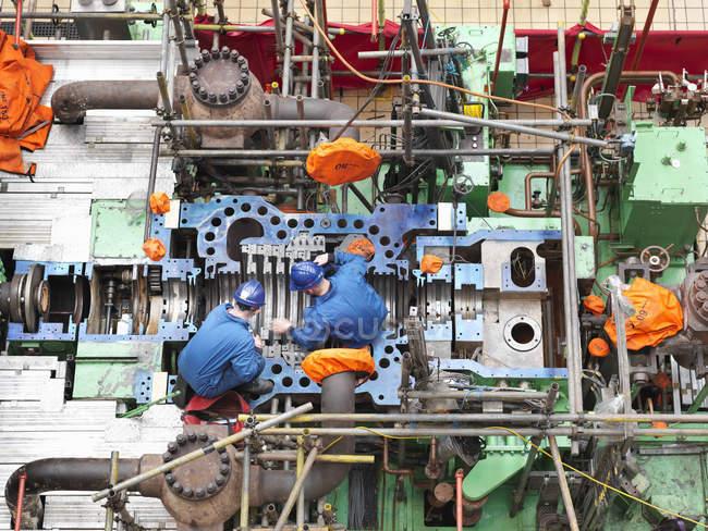 Ingénieurs inspectant la réparation du carter de turbine pendant la panne de la centrale, vue aérienne — Photo de stock