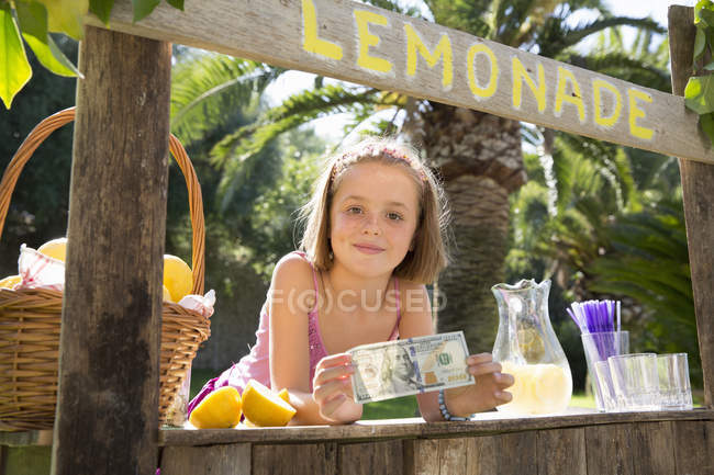 Retrato de muchacha en el puesto de limonada sosteniendo el billete de cien dólares - foto de stock