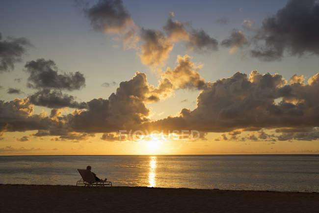 Person resting on beach with beautiful sunset on horizon over sea — Stock Photo