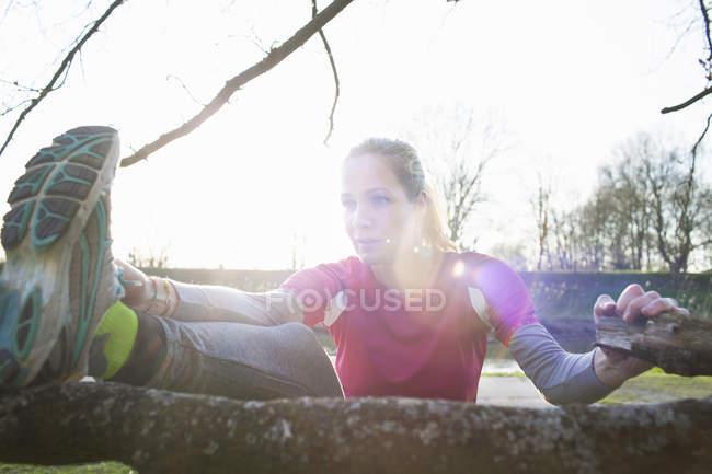 Woman leg raised on tree branch stretching — Stock Photo