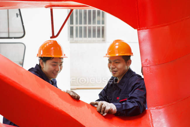 Workers looking at quality of work in crane manufacturing facility, China — Stock Photo