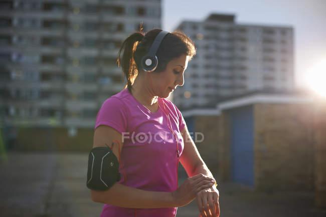 Зрелые женщины бегун, проверка наручные часы в сумерках — стоковое фото