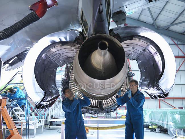 Ingenieros trabajando en motores a reacción en fábrica de mantenimiento de aeronaves - foto de stock
