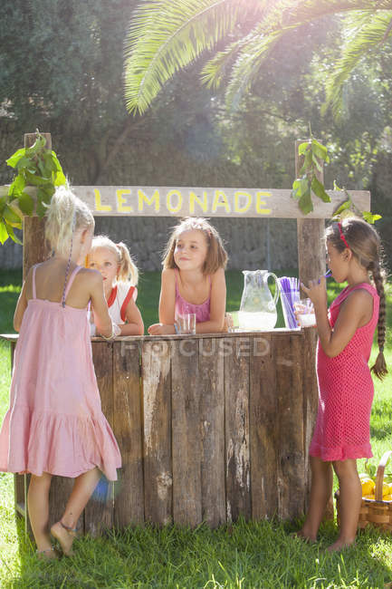 Four girls buying and selling at lemonade stand in park — Stock Photo