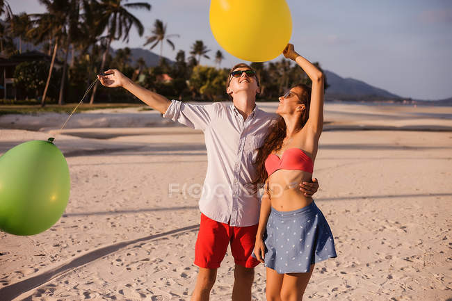 Young couple on beach looking up at balloons, Koh Samui, Thailand — Stock Photo