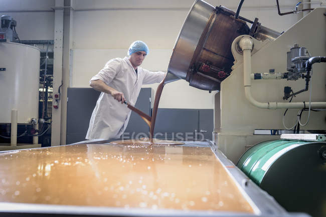Worker pouring confectionery fudge in chocolate factory — Stock Photo