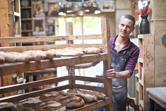 Portrait of young male baker with shelves of fresh bread — Stock Photo
