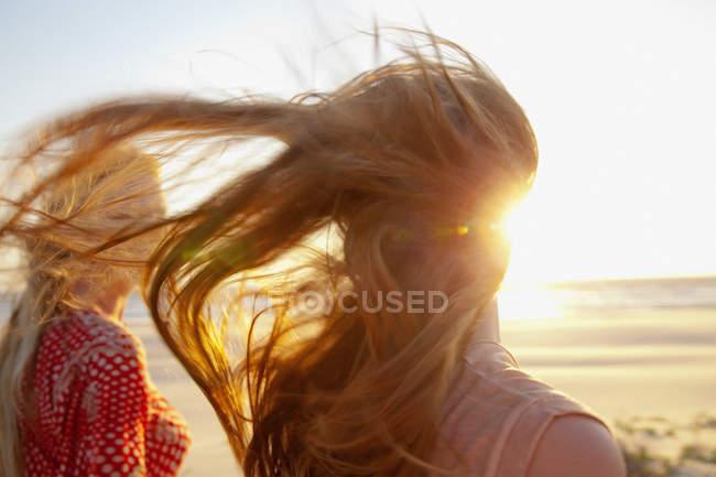 Madre e figlia a piedi sulla spiaggia ventosa — Foto stock