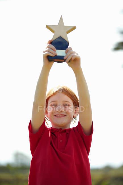 Fille acclamant avec trophée à l'extérieur — Photo de stock