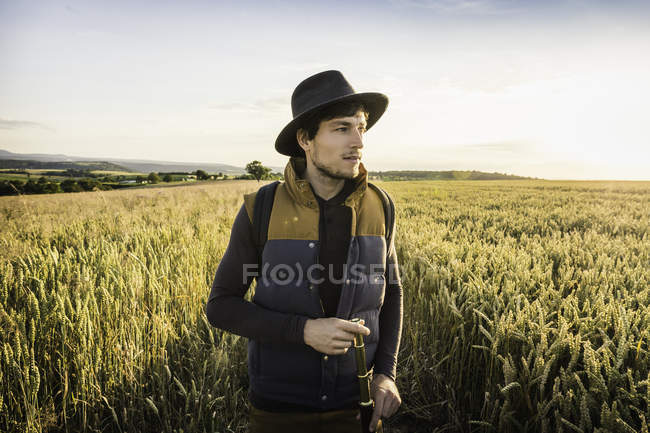 Mid adult man, standing in field, holding telescope, Neulingen, Baden-Wuerttemberg, Germany — Stock Photo