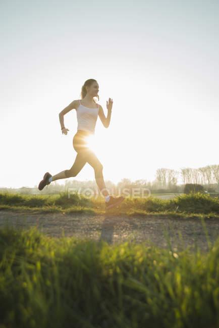 Young female runner on sunlit dirt track — Stock Photo