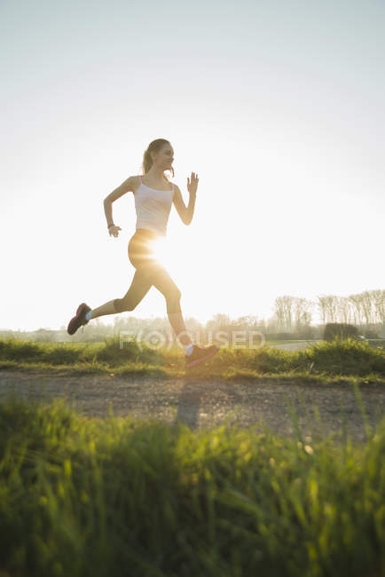 Young female runner on sunlit dirt track — Stock Photo