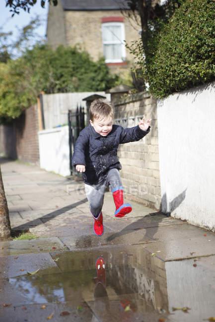 Criança masculina em botas de borracha vermelha pulando na poça da calçada — Fotografia de Stock