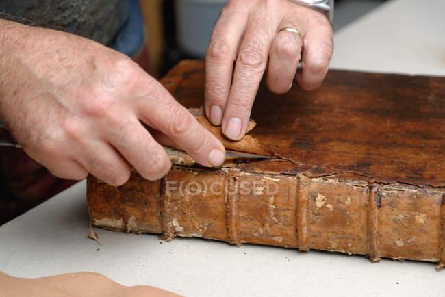 Mãos de sênior masculino encadernador tradicional, removendo o couro do livro — Fotografia de Stock