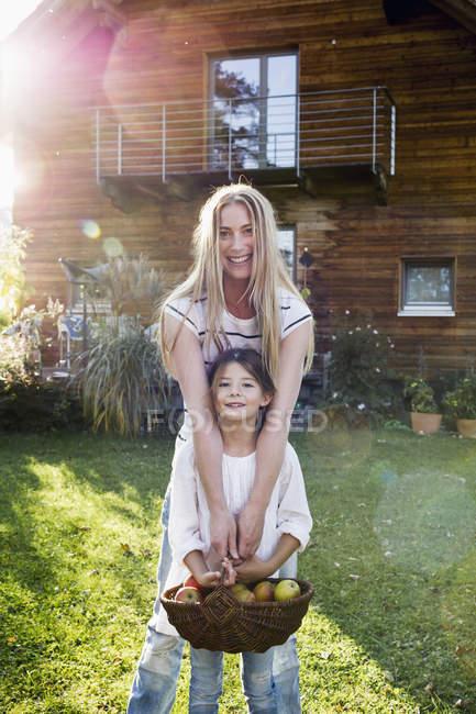 Mãe e filha segurando cesta de maçãs — Fotografia de Stock