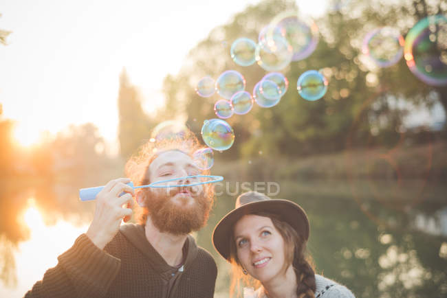 Young couple blowing bubbles — Stock Photo