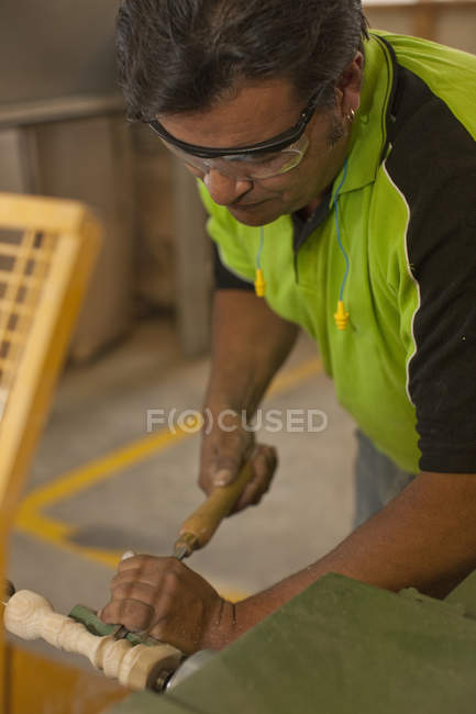 Carpenter turning wood with chisel in workshop — Stock Photo