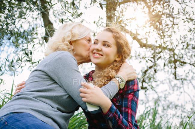Мати цілуватися дочки-підлітка на щоці — стокове фото