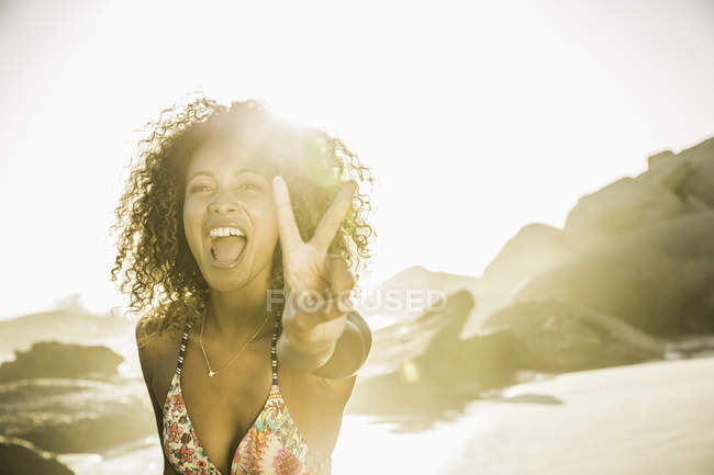 Happy woman showing peace sign on beach — Stock Photo