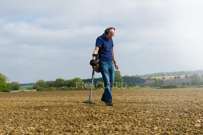 Reifer Mann mit Kopfhörern Suche schlammigen Feld mit Metalldetektor — Stockfoto