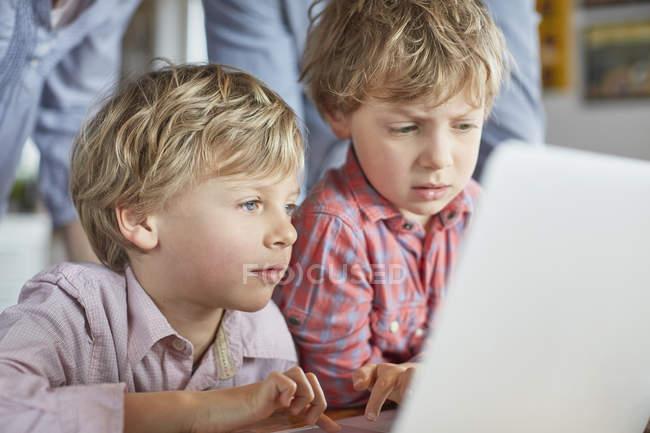 Meninos usando laptop juntos em casa — Fotografia de Stock